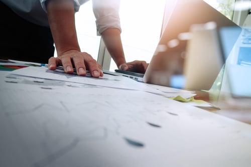 henkilö on tietokoneella tekemässä suunnitelmia keräämänsä tiedon pohjalta Kuva Shutterstock