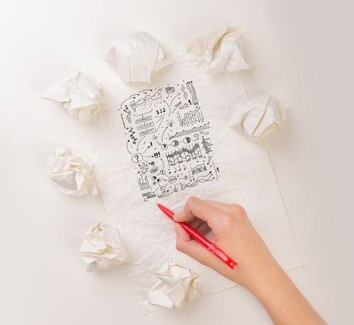 ihminen piirtää luonnosta ympärillä hylättyjä suunnitelmia Kuva Shutterstock