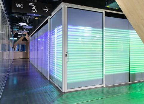 Oodin Kuutio-immersiivitilan älylasiseinät joissa läpinäkyvä projisointikalvo ja kosketusominaisuus