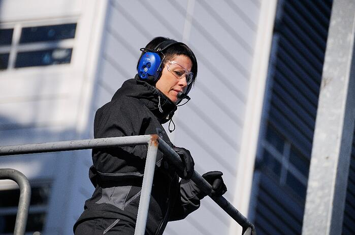 nainen valvoo tehdasympäristöä viestintäkuulosuojaimet päässään Kuva Peltor