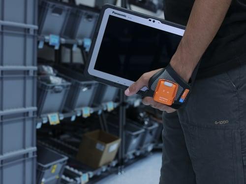 varastotyöntekijä kantaa kädessään Panasonic Toughbook A3:a Kuva ProGlove