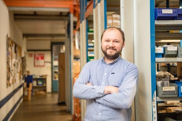 Raskoneen IT Team Manager Maxim Demin seisoo varastohyllyjen vieressä Kuva Paula Ojansuu