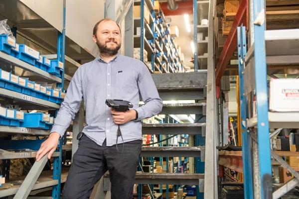 Raskoneen IT Team Manager Maxim Demin seisoo varaston portailla Panasonic-päätelaite kädessään Kuva Paula Ojansuu