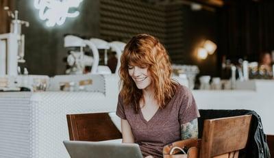 hymyilevä nainen tekee töitä kahvilassa Credit: Brooke Cagle Unsplash