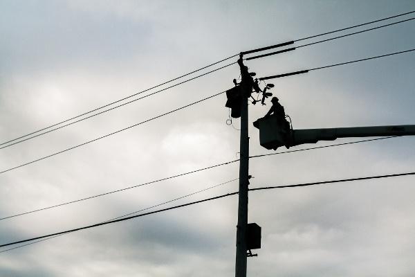 ihminen lyhtypylvästä korjaamassa nosturilta käsin Credit American Public Power Association Unsplash