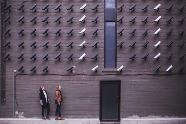 kaksi henkilöä seisoo kymmenien valvontakameroiden kuvattavana Matthew Henry Unsplash