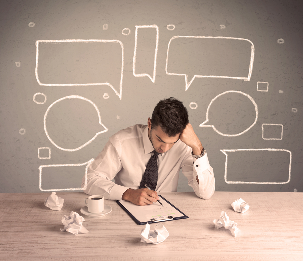 An intelligent elegant business person sitting at a desk and working with drawn empty text bubbles, boxes around him concept