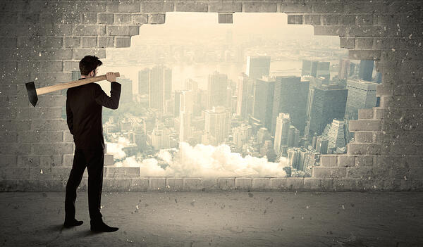 Business man hitting wall with hammer on city view background-1