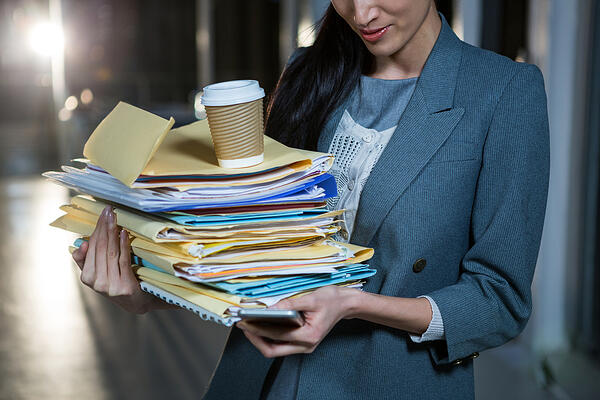 Businesswoman carrying stack of file folders while using mobile phone in the office Credit: Shutterstock
