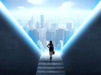 nainen tuijottaa salkku kädessään virtuaalista kaupunkinäkymää Kuva: Shutterstock