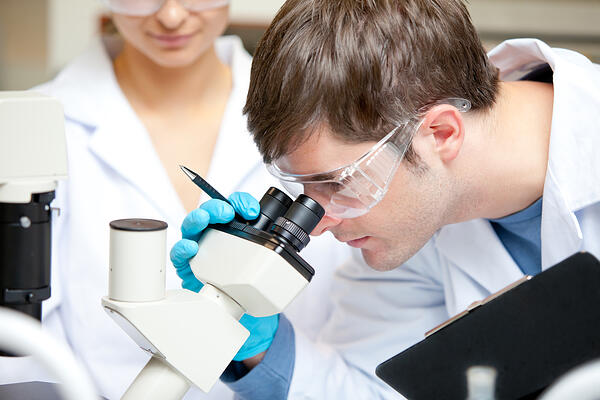 Caucasian male scientist holding pen and clipboard looking through a microscope in his laboratory Image: Shutterstock