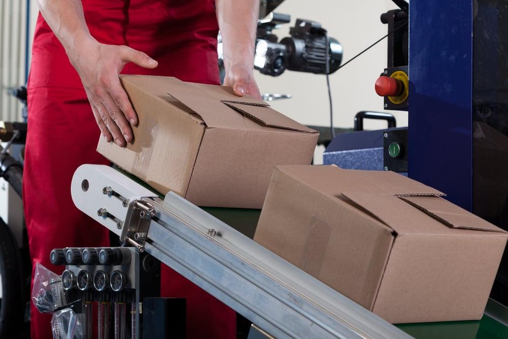 ihminen laskee pakettia kuljetinhihnalle lajittelussa Kuva: Shutterstock