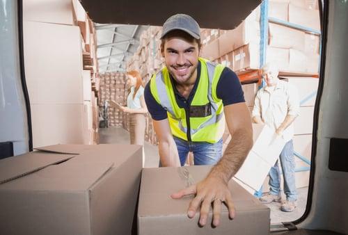 hymyilevä ihminen nostaa laatikkoa autosta Kuva Shutterstock