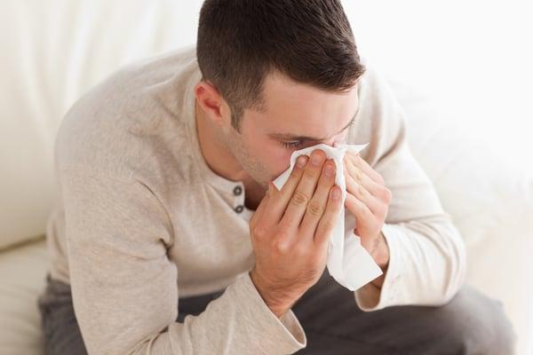 mies niistää nenää sohvalla istuen Kuva: Shutterstock