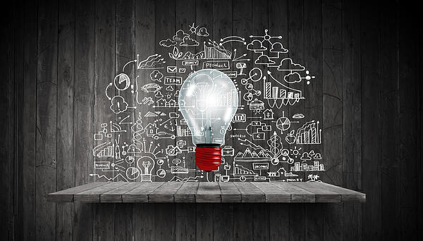 Light bulb and drawing business strategy at background
