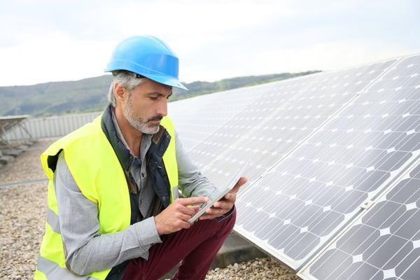 huoltomies tarkistaa aurinkopaneelien toimivuutta ja on yksin töissä katolla Kuva: Shutterstock