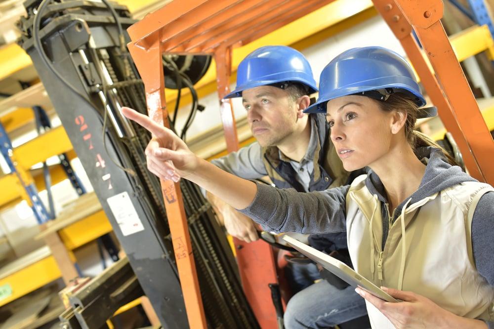 operaattori osoittaa trukkikuskille hyllypaikkaa varastossa Kuva: Shutterstock