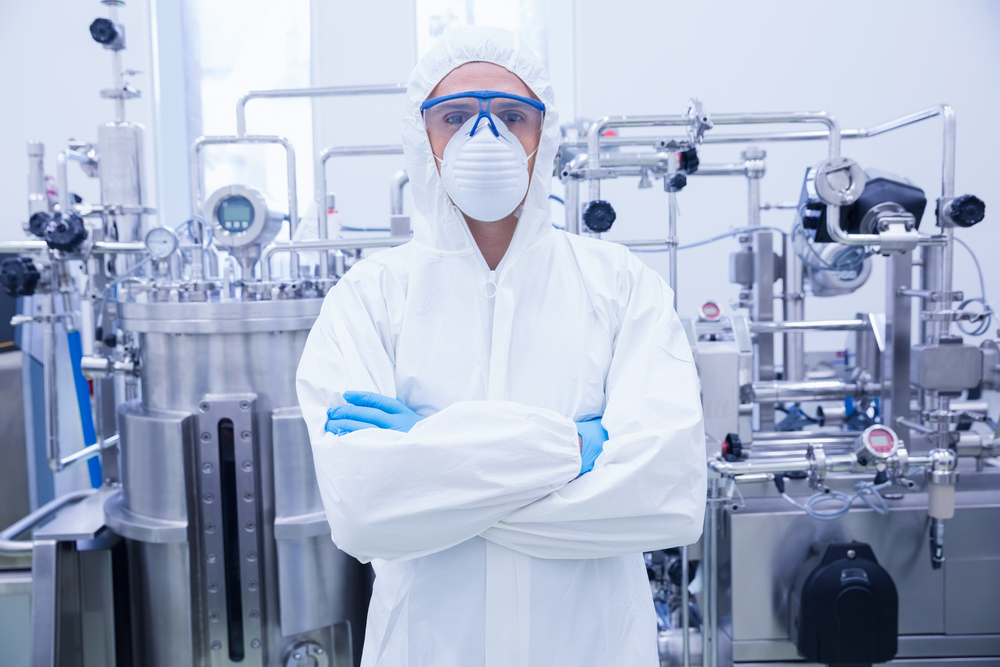 Scientist in protective suit standing with arms crossed in the factory Image: Shutterstock
