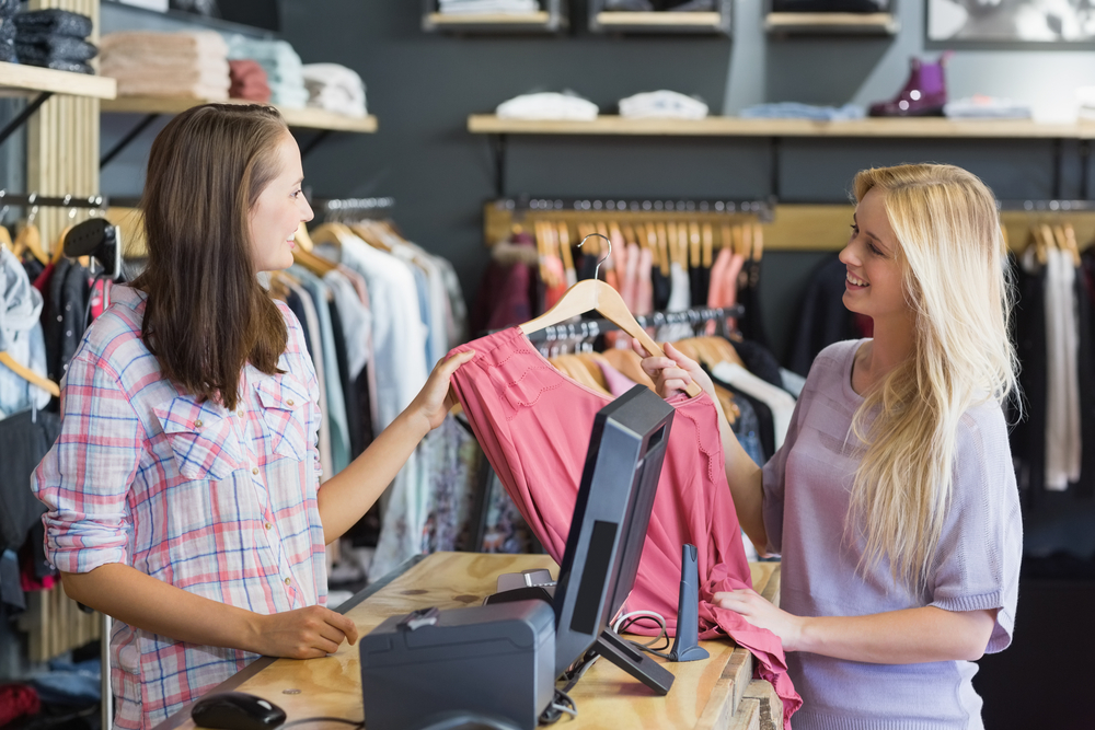 Smiling blonde doing shopping in clothes store Image: Shutterstock