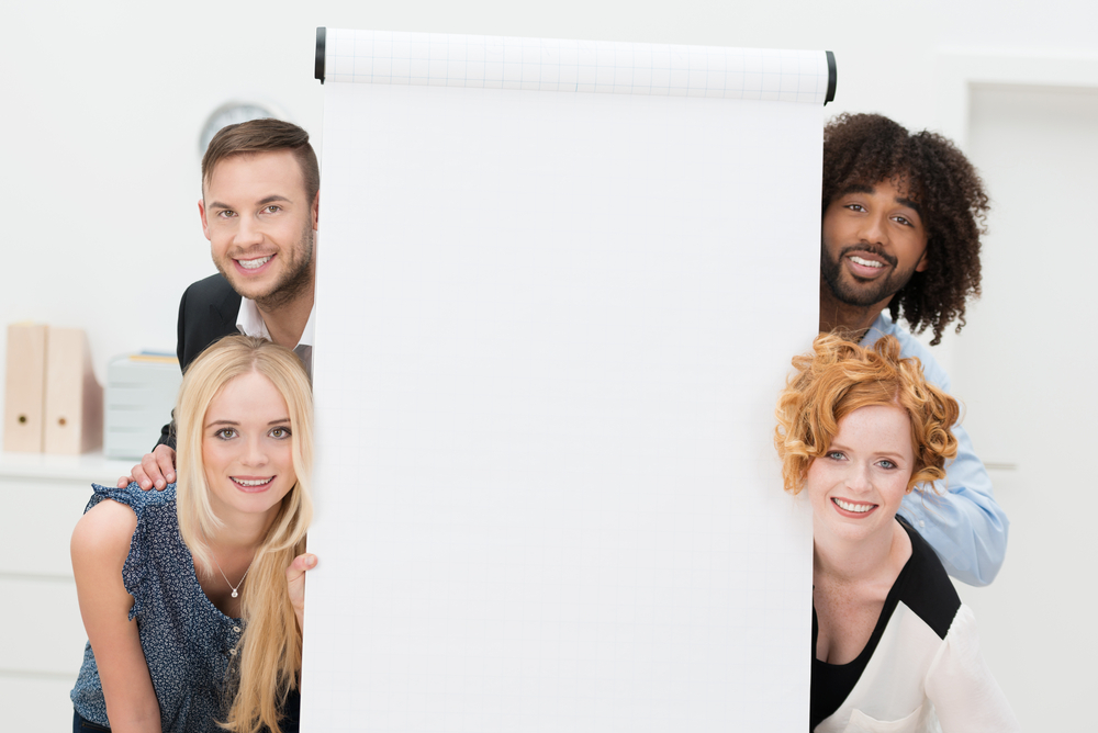 Smiling successful multiethnic business team with a blank white sheet of paper on a flip chart peering playfully around the sides at the camera