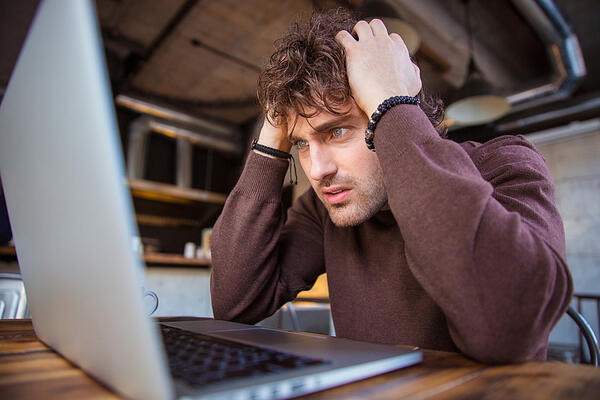 Stressful upset desperate handsome curly man in brown sweetshirt working using laptop and having headache Credit: Shutterstock
