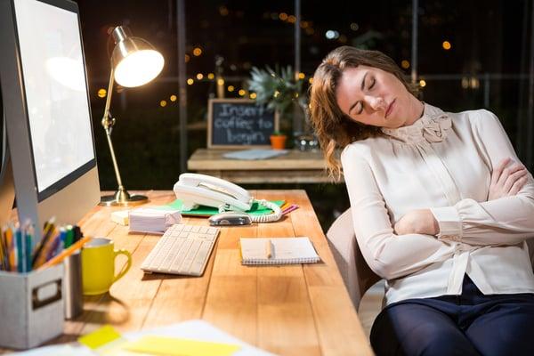 väsynyt nainen nukkuu työpöydän ääressä toimistolla Kuva: Shutterstock