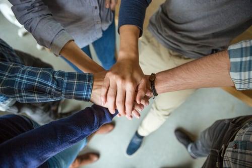ihmiset liittävät kädet yhteen symbolina yhteistyöstä Kuva Shutterstock