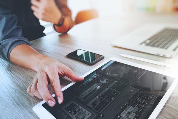 Website designer working digital tablet and computer laptop with smart phone and graphics design diagram on wooden desk as concept Credit: Shutterstock
