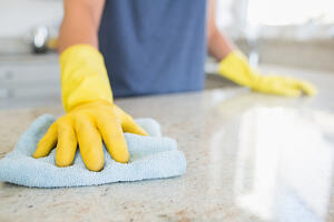 Woman cleaning the counter in the kitchen Image: Shutterstock
