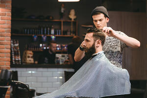 Young handsome barber making haircut of attractive bearded man in barbershop Image: Shutterstock