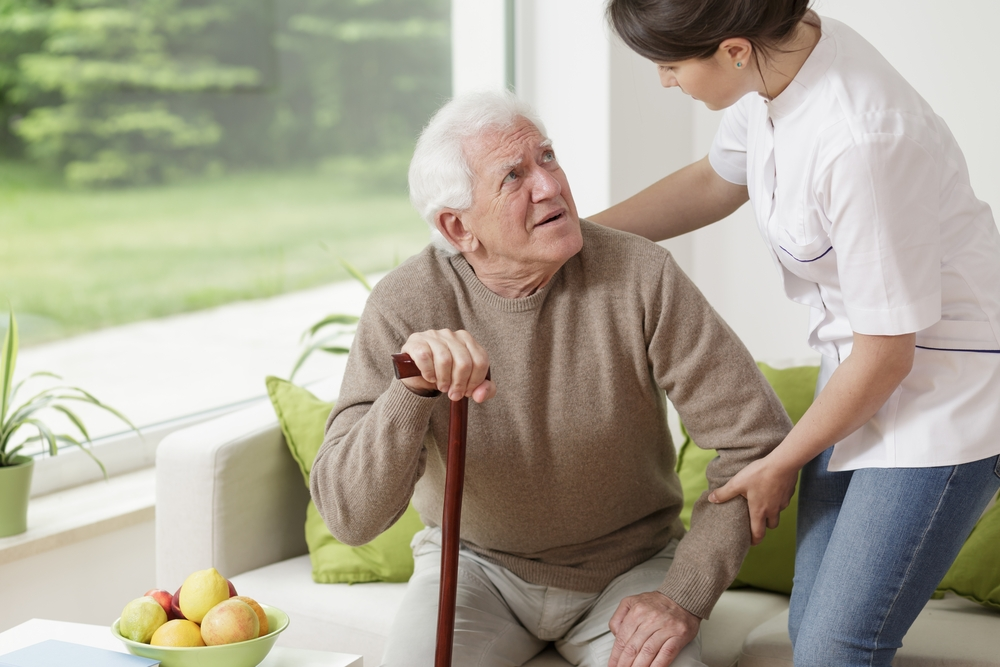 Young woman helping old man to stand up Image: Shutterstock