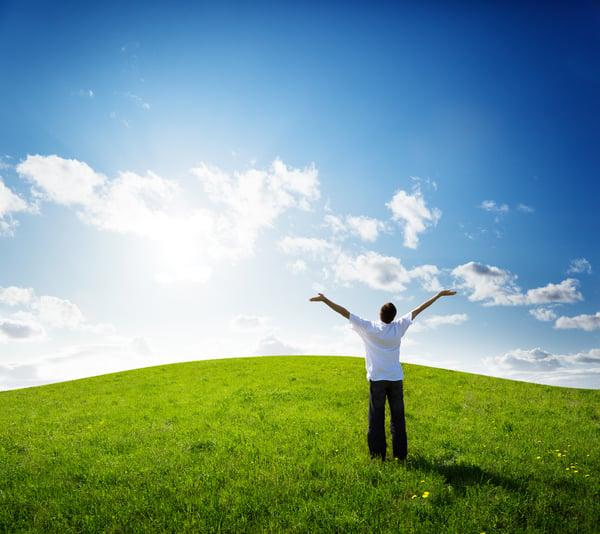 mies tervehtii aurinkoa iloisesti keskellä peltoa ja kesäistä päivää Kuva: Shutterstock