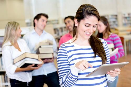 nuori opiskelija käyttää tablettia kun selän takana kaverit kantavat kirjoja Kuva Shutterstock