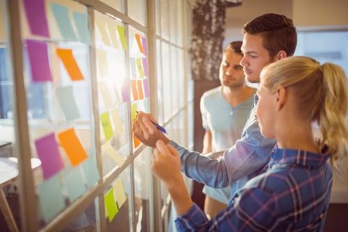nuoret tekevät yhteistyötä muistilapputaulun edessä Kuva Shutterstock