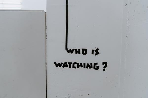 Who is watching -teksti seinässä Credit: Claudio Schwarz @purzlbaum Unsplash