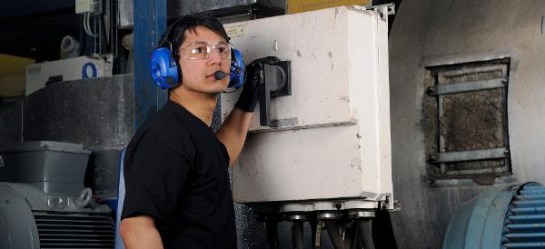 Mies käyttää hallintalaitteita teollisuusympäristössä viestintäkuulosuojaimet päässään Kuva: Peltor