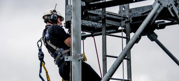 Henkilö kiipeää mastoon yksin viestintäkuulosuojaimet päässään Kuva: Peltor