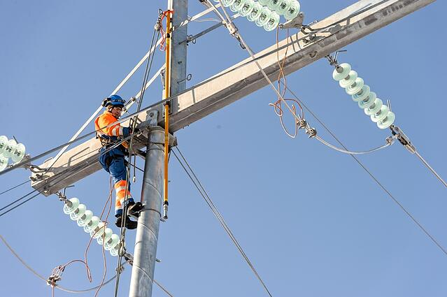 mies tekee töitä korkealla sähkötolpassa