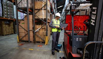mies-seisoo-varastossa-trukin-vieressä-Panasonic-kannettava-kädessä