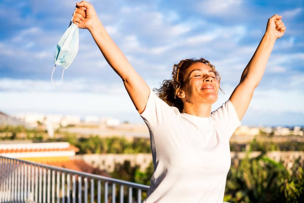 nainen iloitsee luovuttuaan kasvomaskista AdobeStock