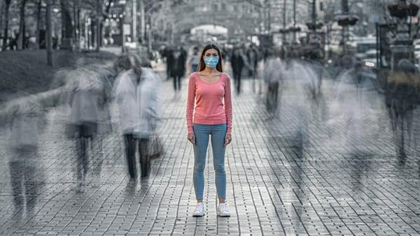nainen seisoo keskellä ihmisvilinää kasvomaski kasvoillaan AdobeStock