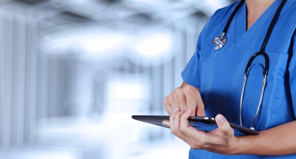 terveydenhuollon ammattilainen käyttää tablettia leikkaussaliympäristössä Kuva Shutterstock