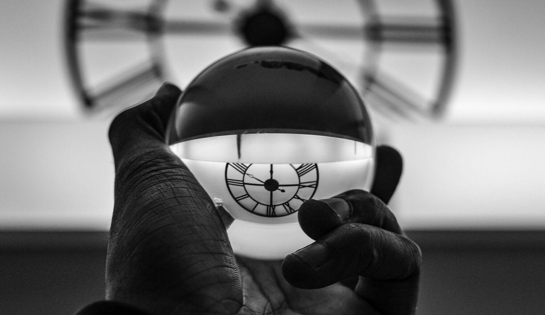 käsi joka pitelee kellonaikaa heijastavaa lasipalloa Credit: Jossuha Theophile Unsplash
