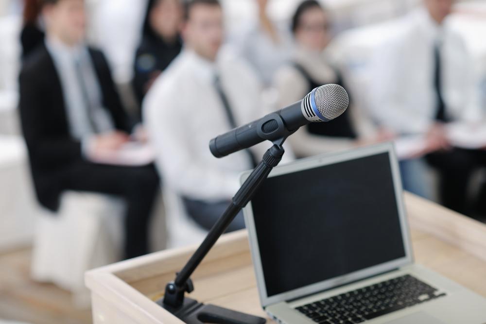 puhujapönttö jossa mikrofoni ja tietokone Kuva: Shutterstock